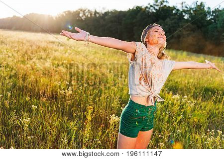 happy young woman standing with open arms and closed eyes at holi festival in field