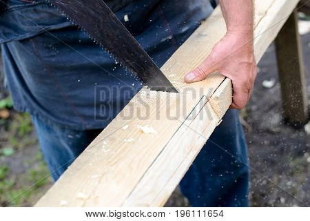 A man sawing a board with a handsaw