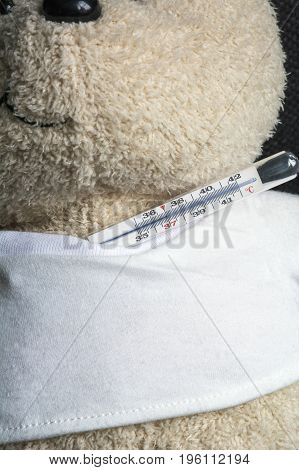 Creamy white toy bear with usual thermometer