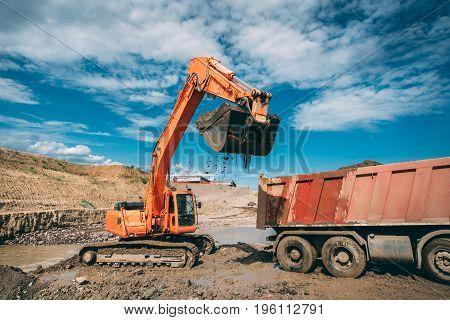 excavator bulldozer loading dumper truck during highway construction site