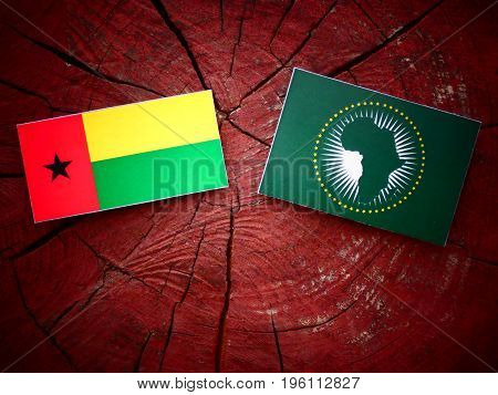 Guinea Bissau Flag With African Union Flag On A Tree Stump Isolated