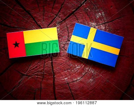 Guinea Bissau Flag With Swedish Flag On A Tree Stump Isolated