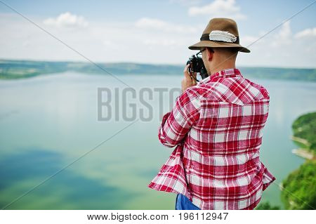 Portrait Of A Stunning Man In Casual Clothing With A Hat Posing With An Old Camera On The Rock With