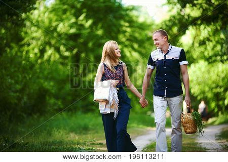 in love couple walking in forest. blonde girl in dark blue dress with plaid and man in light trousers with wicker basket. happy family relationship concept