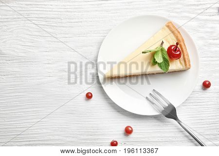 Plate with delicious cheesecake and cherry on white table