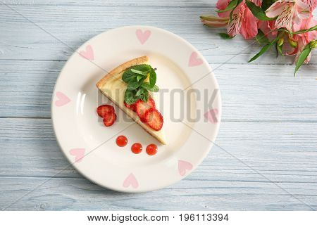 Plate with delicious cheesecake and sliced strawberry on wooden table