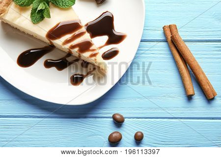 Plate with delicious cheesecake, chocolate and mint on blue wooden table