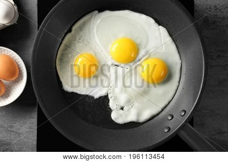 Delicious over easy eggs in pan on stove