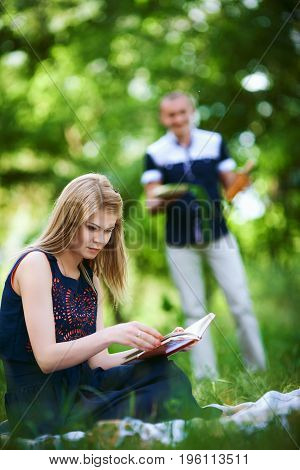 Young couple on vacation. blonde girl in dark blue dress read the book and man in light trousers with surprise in his hands on background. happy family relationship concept