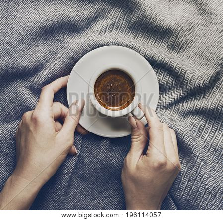 Woman hands holding tasty coffee espresso in small cup on grey plaid. Home concept. Top View.