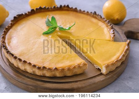 Wooden board with delicious lemon pie on gray table, closeup
