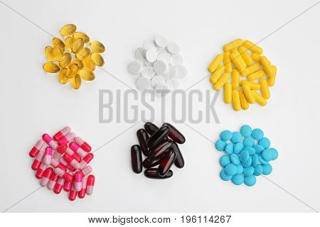 Composition with different colorful pills on white background