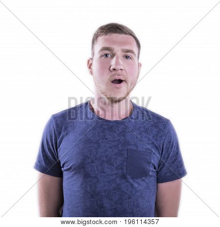 A tired young man standing isolated over the white background. A yawning student in a saturated blue t-shirt. A melancholic, sad, exhausted guy. A stressed and ill male.
