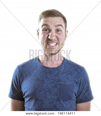 An angry male in a dark blue shirt isolated over the white background. A disappointed young man with a strong facial expressions. A sad scared student with light brown hair.