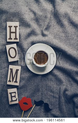 Tasty coffee espresso in small cup on grey plaid with wooden letters home. Home Family concept. Top View.