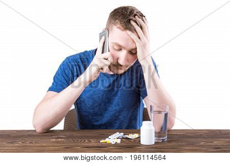 A depressed, sick man calling a phone isolated on a white background. A guy in a blue shirt next to many pills and tablets. A bottle of medicaments and a glass of water on a wooden table.