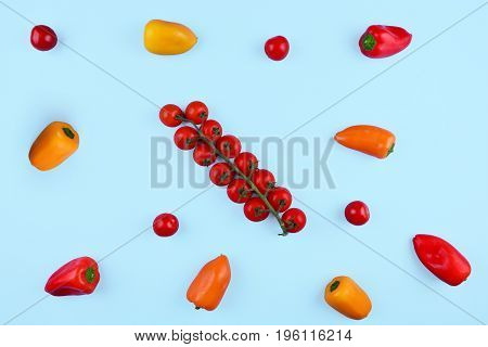 Cherry tomatoes and paprika on trendy blue background. Top view. Colorful diet and healthy food concept.