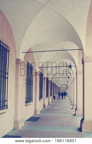 Ancient porticos on the background of city Bologna in Italy