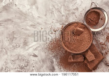 Chopped chocolate chunks and bowl with  cocoa powder on table