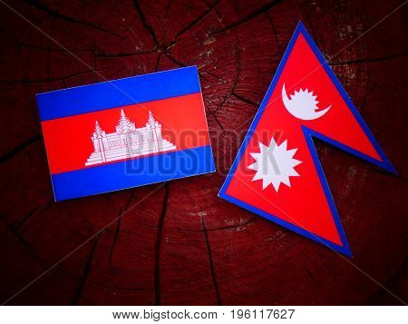 Cambodian Flag With Nepali Flag On A Tree Stump Isolated