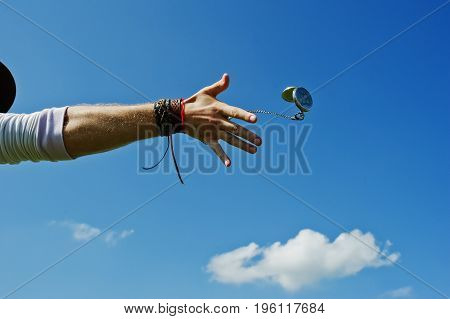 Male hand throwing oldschool watch away agaisnt sky
