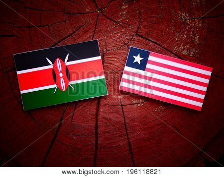 Kenyan Flag With Liberian Flag On A Tree Stump Isolated