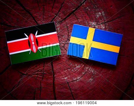 Kenyan Flag With Swedish Flag On A Tree Stump Isolated