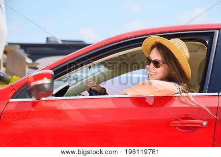 Woman Driver In Hat Travels In Red Car And Smiling