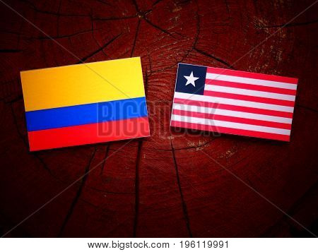 Colombian Flag With Liberian Flag On A Tree Stump Isolated