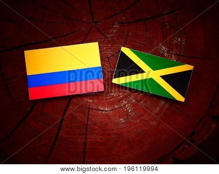 Colombian Flag With Jamaican Flag On A Tree Stump Isolated