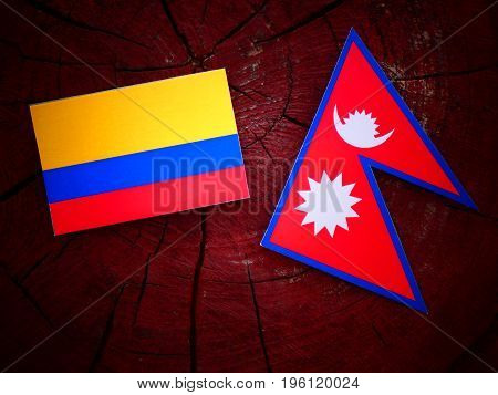 Colombian Flag With Nepali Flag On A Tree Stump Isolated