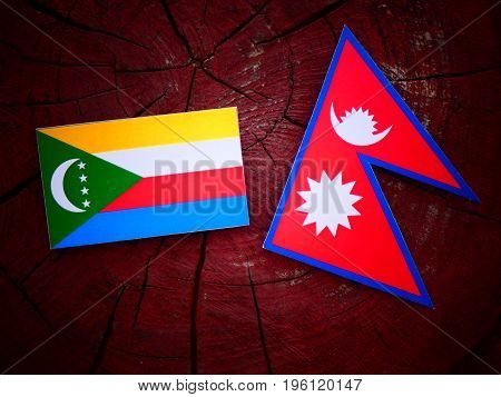 Comoros Flag With Nepali Flag On A Tree Stump Isolated
