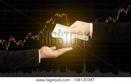 Hand holding money transfer with graph stock market blurred background Finance and investment concept