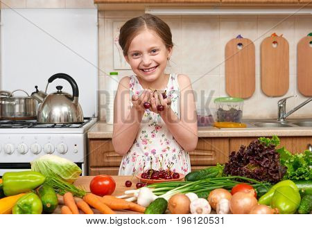 child girl posing with handful of cherries, fruits and vegetables in home kitchen interior, healthy food concept