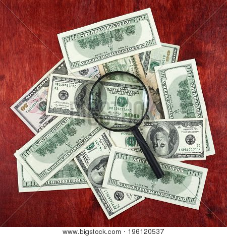 Magnifier placed on center of money dollar and wood background, business concept