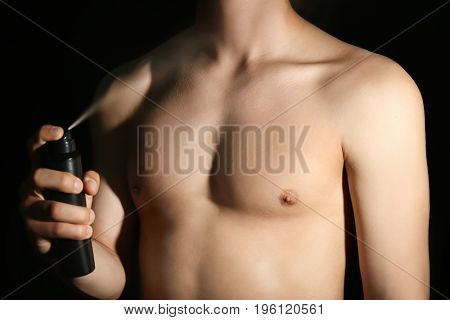 Handsome young man with deodorant on dark background, closeup