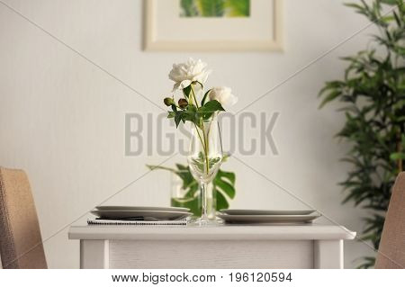 Beautiful table setting with peony flowers in cafe