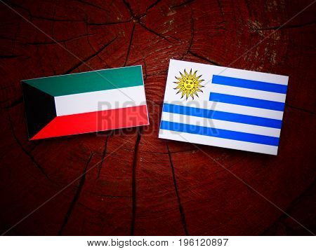 Kuwaiti Flag With Uruguaian Flag On A Tree Stump Isolated