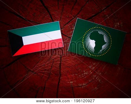 Kuwaiti Flag With African Union Flag On A Tree Stump Isolated
