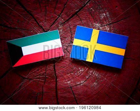 Kuwaiti Flag With Swedish Flag On A Tree Stump Isolated