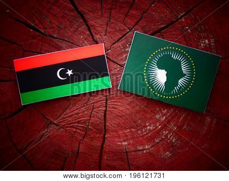 Libyan Flag With African Union Flag On A Tree Stump Isolated