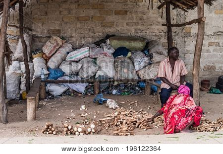 Zanzibar, Tanzania - July 15, 2016: People of zanzibar selling ginger roots and spices right in the street, garbage behind them