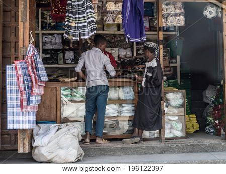 Zanzibar, Tanzania - July 15, 2016: Street trade on zanzibar, two boys selling clothing and garments for muslim people, tanzania