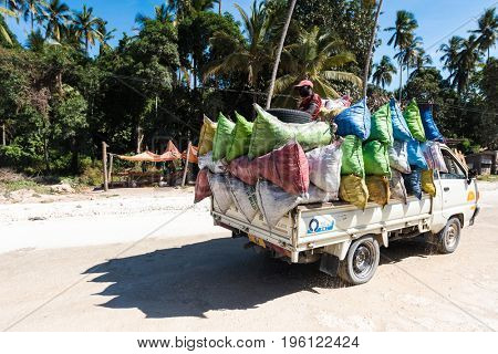 Zanzibar, Tanzania - July 14, 2016: Local man from Zanzibar, tanzania in truck full of bags going to the local market