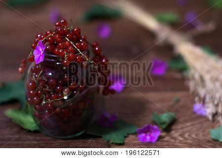 Berries of a currant in a glass jar on a wooden background