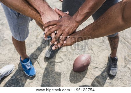group of young multicultural men holding hands before football game