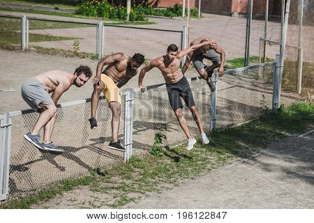 Group Of Young Handsome Men Jumping Over Fence On Court