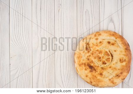 Uzbek bread on old white wooden table. Top view.