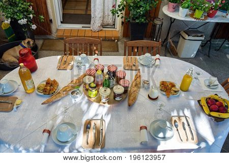 SISTERON FRANCE - JUNE 18 2017: Typical french breakfast in Provence. Table with red tablecloth baguette jam cheese coffee and orange juice