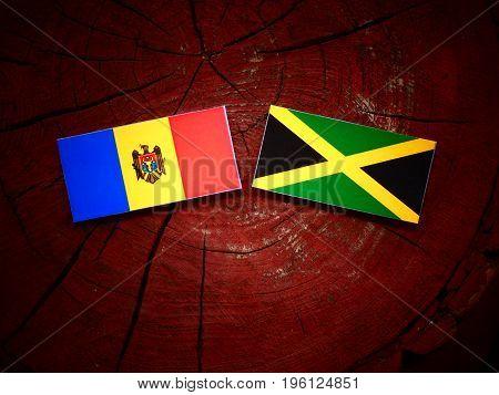 Moldovan Flag With Jamaican Flag On A Tree Stump Isolated